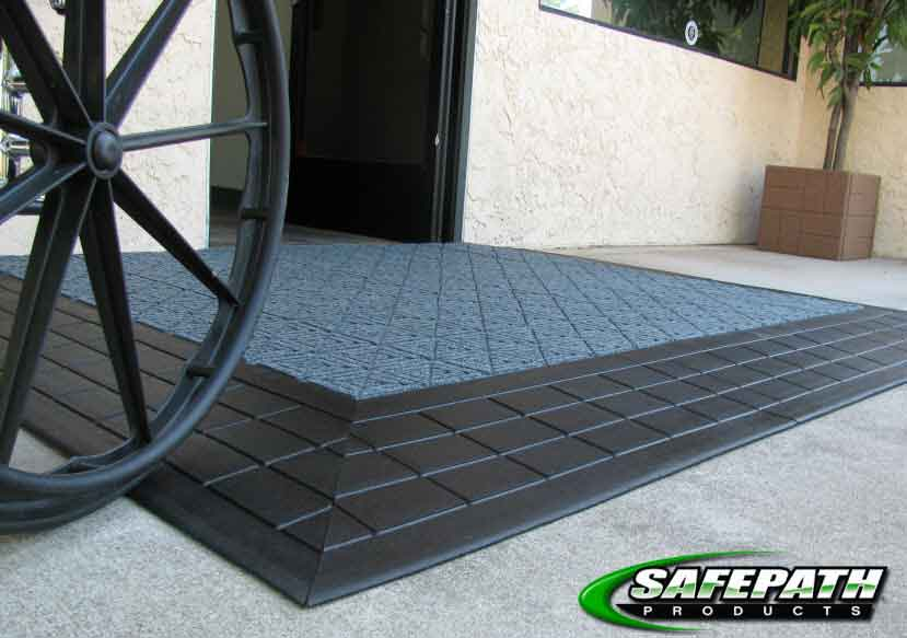 Wheelchair using an ADA compliant door threshold ramp and level landing to access a building